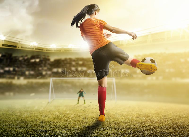 Rear view of asian football player woman in orange jersey kicking the ball in the penalty box. Rear view of asian football player women in orange jersey kicking royalty free stock images