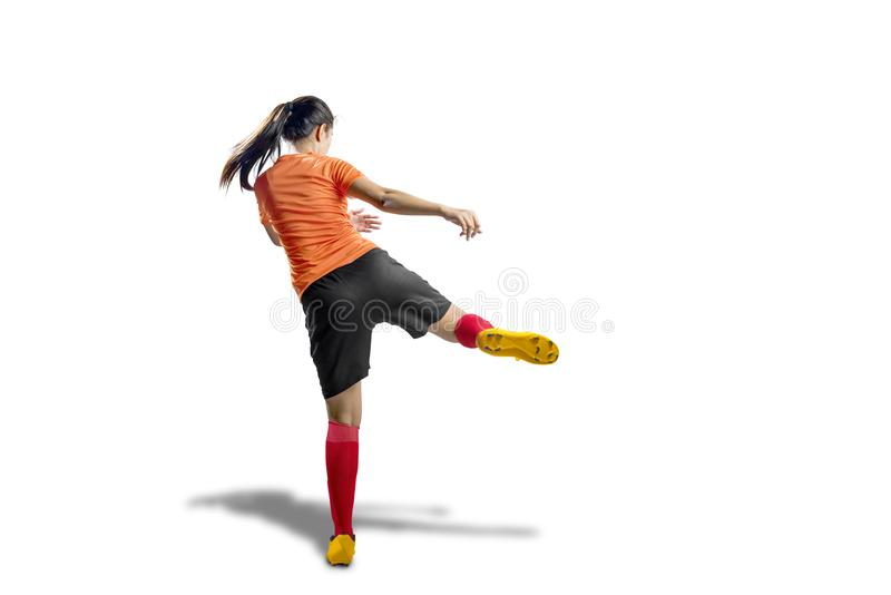 Rear view of asian football player woman in orange jersey with kicking the ball stock images