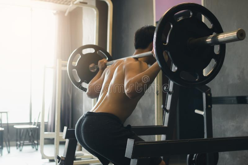 Rear view of asian man performing barbell squats at the indoor g stock photo