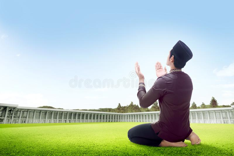 Rear view of asian man sitting in praying position on grass raise the hands and gazing the sky royalty free stock photos