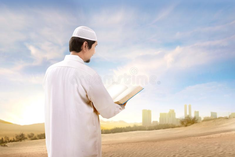 Rear view of asian muslim man with cap standing and reading the quran on the sand. With blue sky background royalty free stock photo