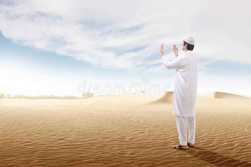 Rear view of asian muslim man raised hands and praying on the sand dune. With blue sky background royalty free stock photo