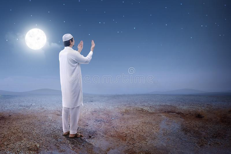 Rear view of asian muslim man raised hands and praying on the sand dune. With moon and night scene background royalty free stock images