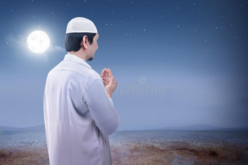 Rear view of asian muslim man raised hands and praying on the sand dune. With moon and night scene background stock images