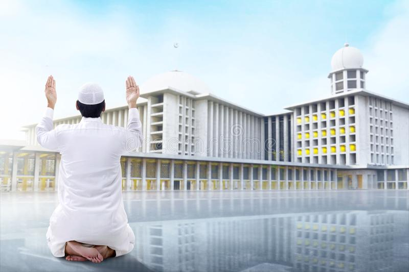 Rear View of Asian Muslim man sitting in pray position while raised hands and praying. Outside the mosque royalty free stock photo