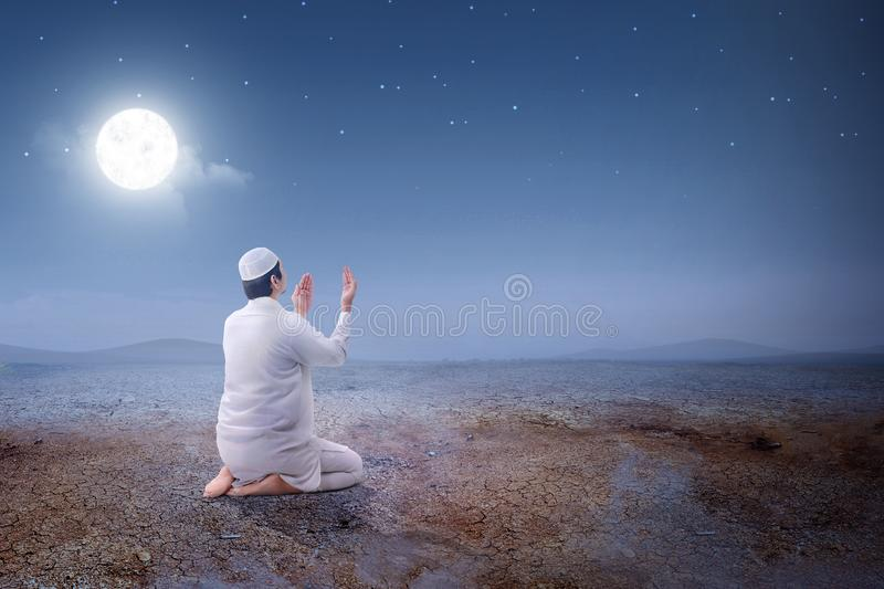 Rear view of asian muslim man sitting in pray position while raised hands and praying on the sand dune. With moon and night scene background royalty free stock image