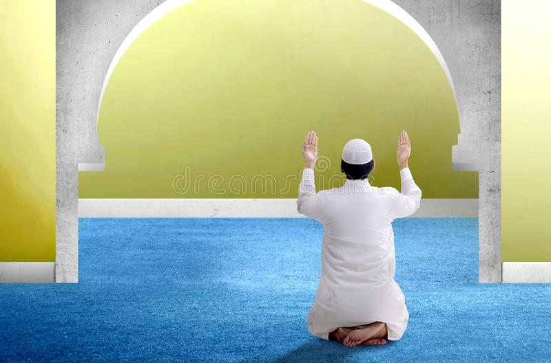 Rear View of Asian Muslim man sitting in pray position while raised hands. And praying inside the mosque stock photos
