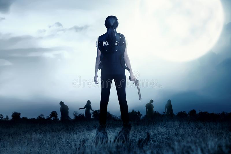 Rear view of Asian policewoman with the gun on her hand face the zombies on the grass field royalty free stock images