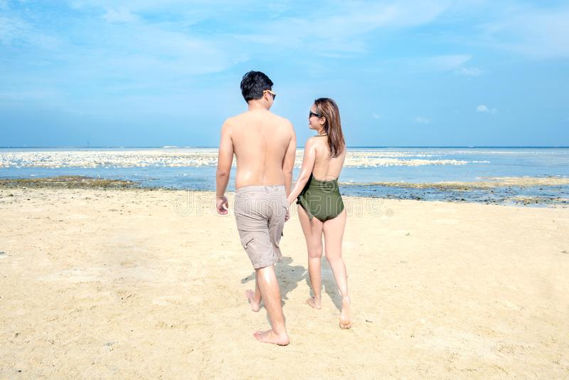 Rear view of asian romantic couple relax and walking on the beach royalty free stock photos
