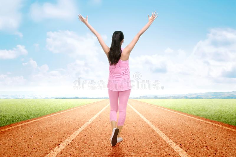 Rear view of Asian runner woman with excited expression after a run on the running track stock photos