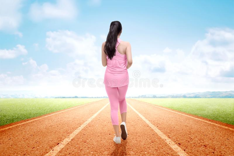 Rear view of Asian runner woman running on the running track stock photo
