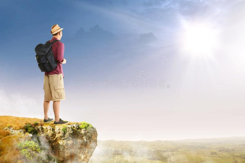 Rear view of asian traveler man with hat and backpack standing on the edge of cliff looking at landscapes royalty free stock photo