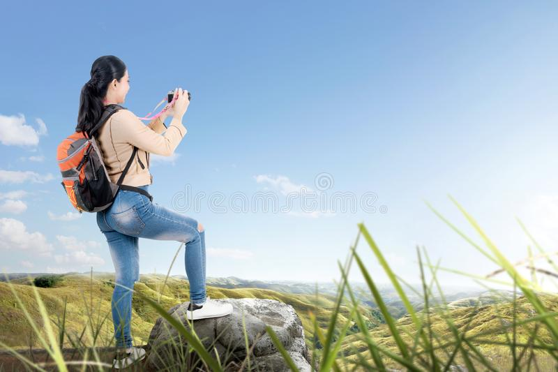 Rear view of Asian woman with a backpack holding a camera to take pictures royalty free stock image