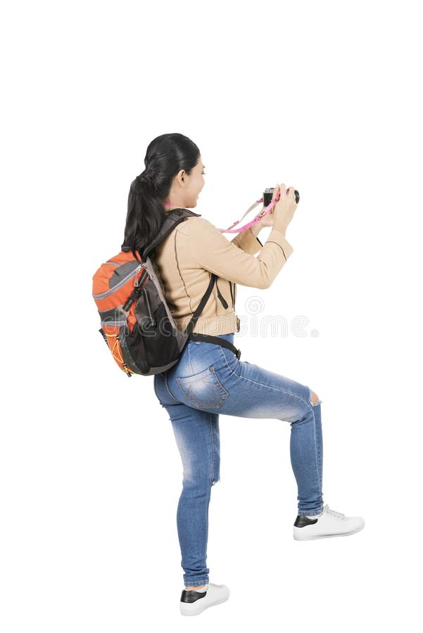 Rear view of Asian woman with a backpack holding a camera to take pictures stock photography