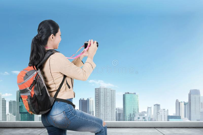 Rear view of Asian woman with a backpack holding a camera to take pictures on the rooftop stock photos