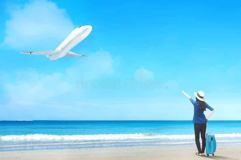 Rear view of asian woman in hat with suitcase bag standing on the beach royalty free stock photography