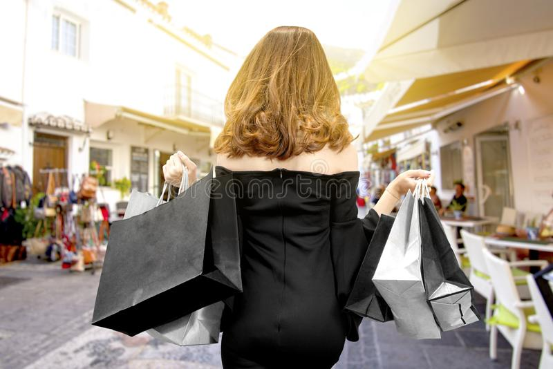 Rear view of an Asian woman holding shopping bags in the city royalty free stock photos