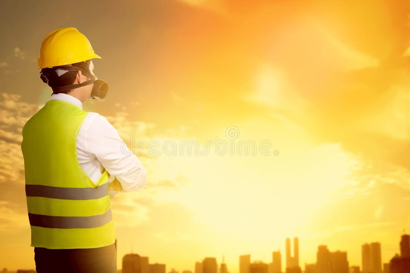 Rear view of asian worker man in safety vest, gloves, yellow helmet and protective mask standing and looking at city. With sunset background stock photo