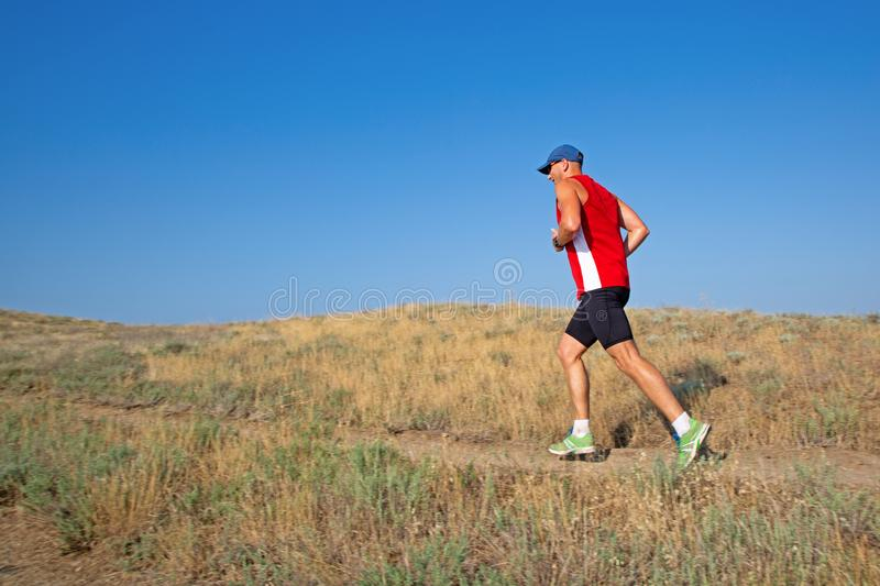 Rear view of athletic runner running on a mountain trail on a blue sky background royalty free stock images