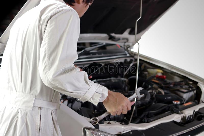 Rear view of automotive mechanic in white uniform with wrench diagnosing engine under hood at the repair garage. Car insurance co. Ncept stock image