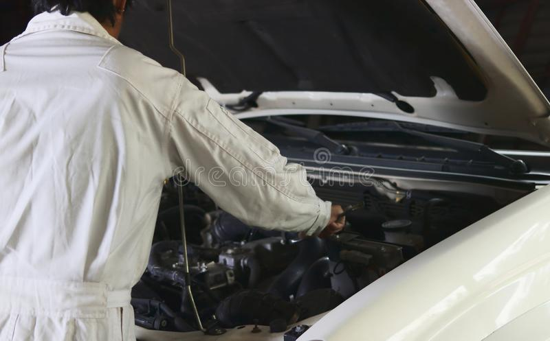 Rear view of automotive mechanic in white uniform with wrench diagnosing engine under hood at the repair garage. Car insurance co. Ncept royalty free stock images