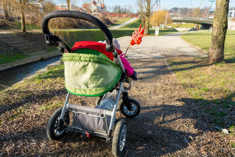 Rear view of a baby stroller with red pinwheel. royalty free stock photography