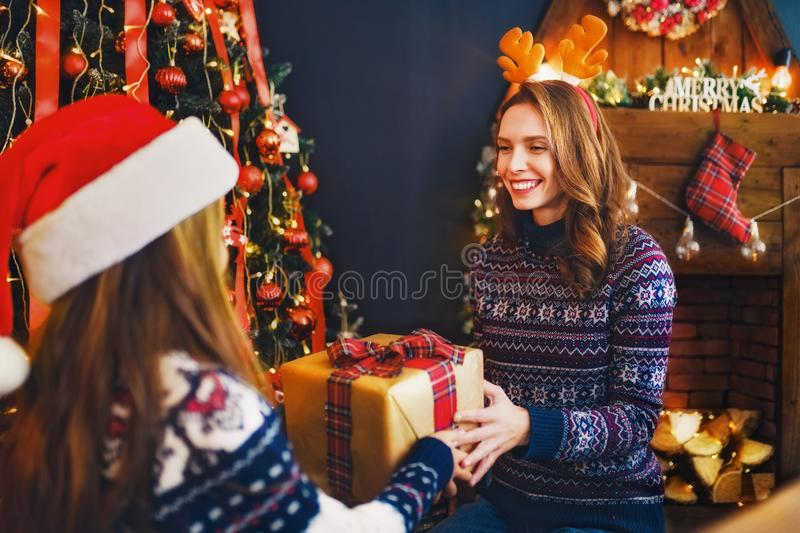 Rear view from the back of a cheerful mom and her cute daughter girl exchanging gifts. royalty free stock photography