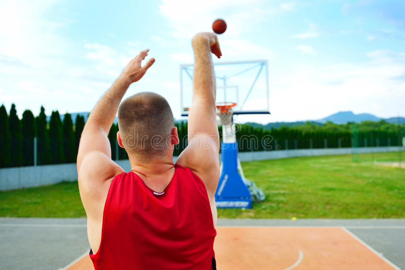Rear view of a basketball player, shooting at basket outdoor royalty free stock image