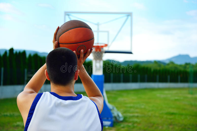 Rear view of a basketball player, shooting at basket outdoor stock photography