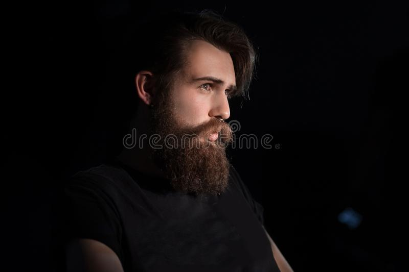 Bearded serious man sitting in a chair stock images