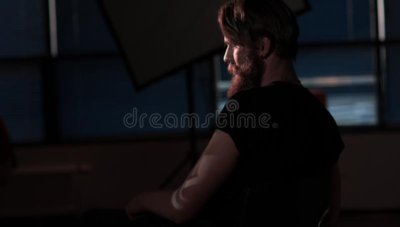 Bearded serious man sitting in a chair royalty free stock images