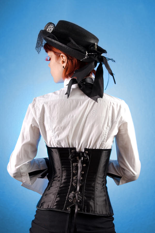Rear view of beautiful girl. In Victorian style clothes, studio shot over blue background royalty free stock images