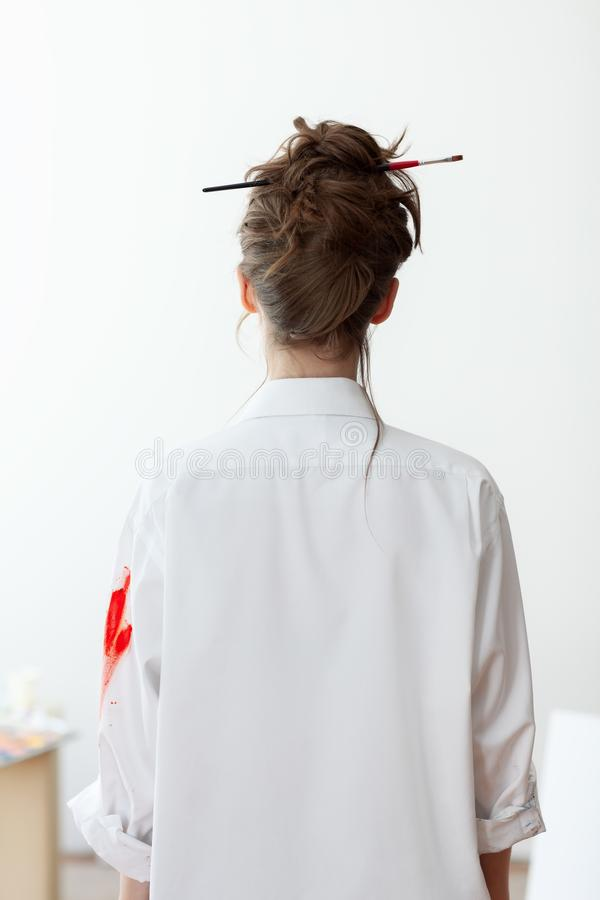 Rear view of beautiful painter woman in white shirt royalty free stock images