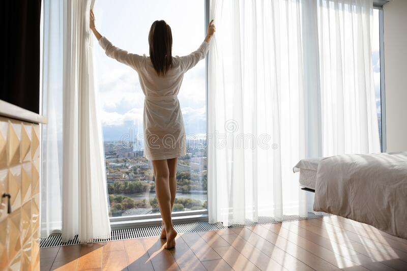 Rear view beautiful woman starting new day, opening curtains royalty free stock images