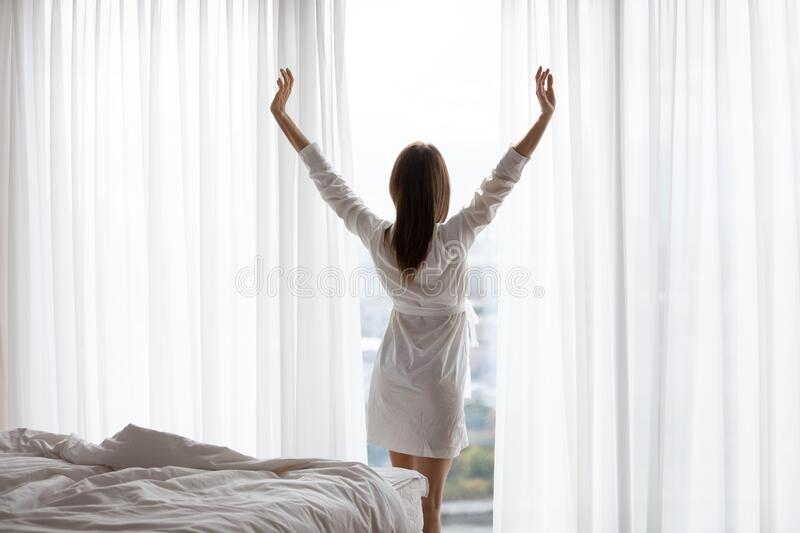 Rear view beautiful woman stretching after awakening, looking out window royalty free stock photos