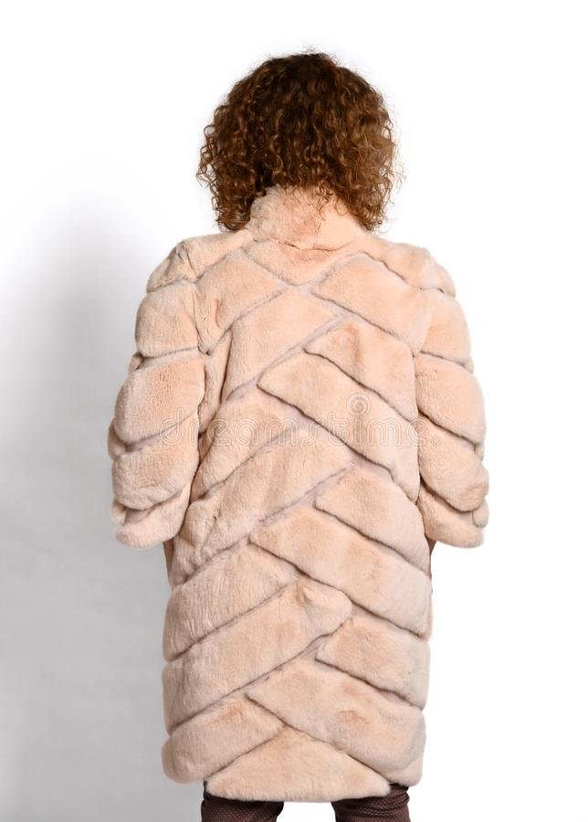Rear view of beige midi fur coat trimmed worn by woman with long curly red hair on white stock images
