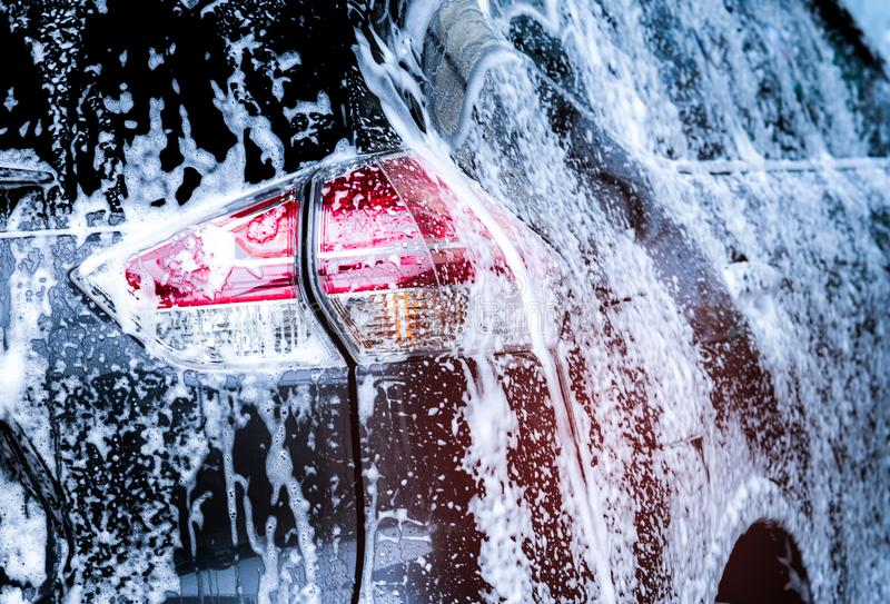 Rear view of black compact SUV car with sport and modern design are washing with water and white foam. Car care service business. stock images
