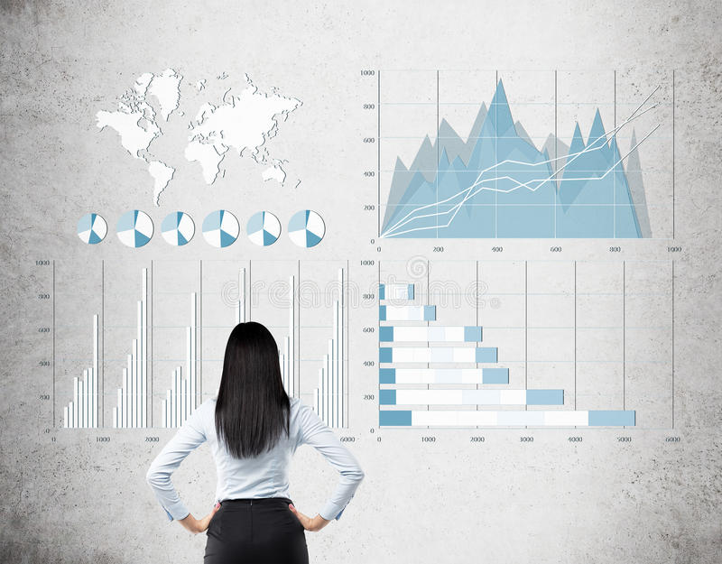 Rear view of black haired woman looking at blue and white graphs. Rear view of a black haired woman looking at white and blue graphs on concrete wall. Concept of stock photography