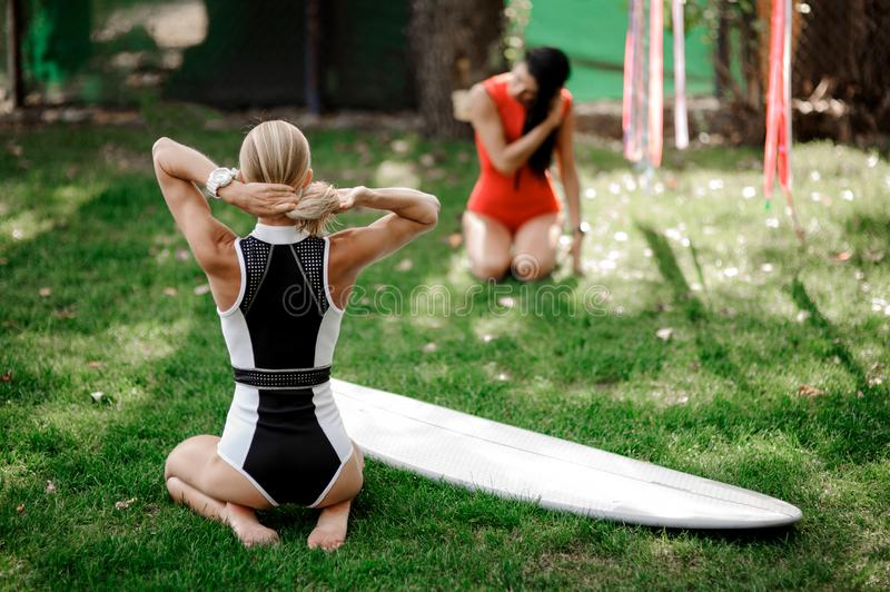 Rear view blonde girl sitting near the wakeboard with another gi. Rear view blonde girl in black and white swimsuit sitting near the wakeboard on the blurred royalty free stock images