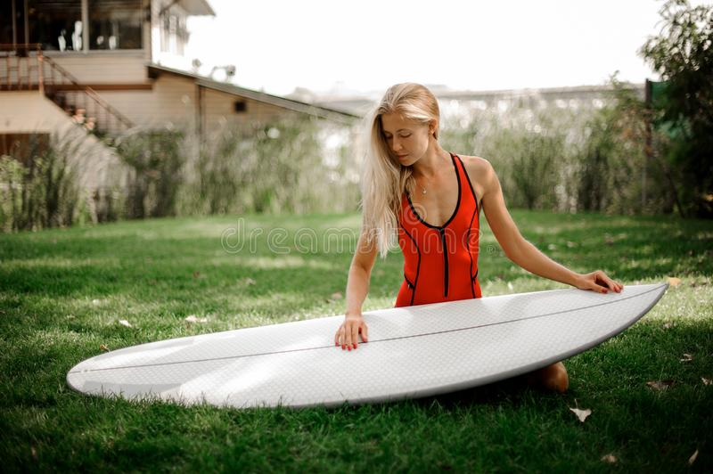 Blonde girl sitting on her knees holding the wakeboard. Rear view blonde girl in red swimsuit standing on her knees holding the wakeboard on the blurred royalty free stock photo