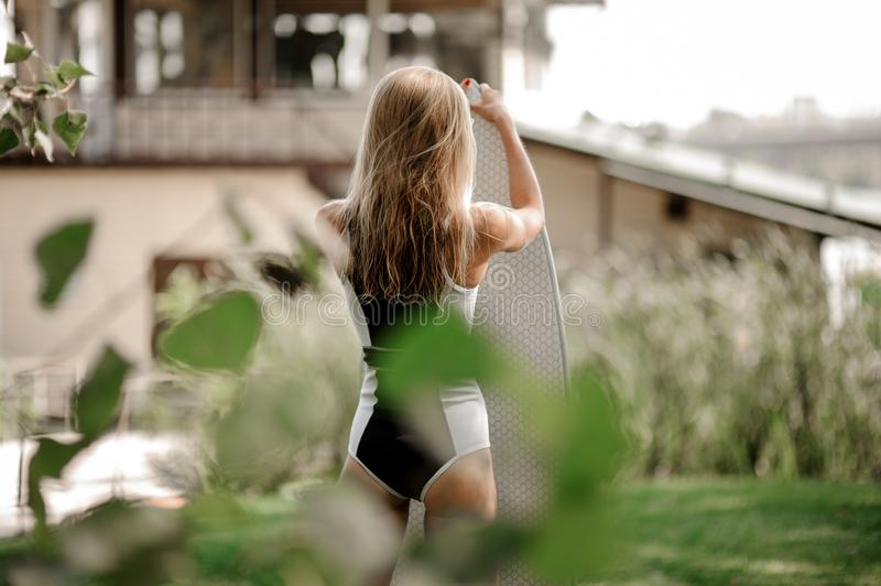 Rear view blonde girl standing with the wakeboard. Rear view blonde girl in black and white swimsuit standing with the wakeboard on the blurred background of old royalty free stock image