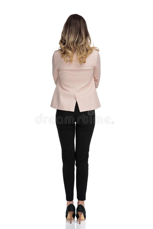 Rear view of blonde smart casual woman in pink suit royalty free stock photos
