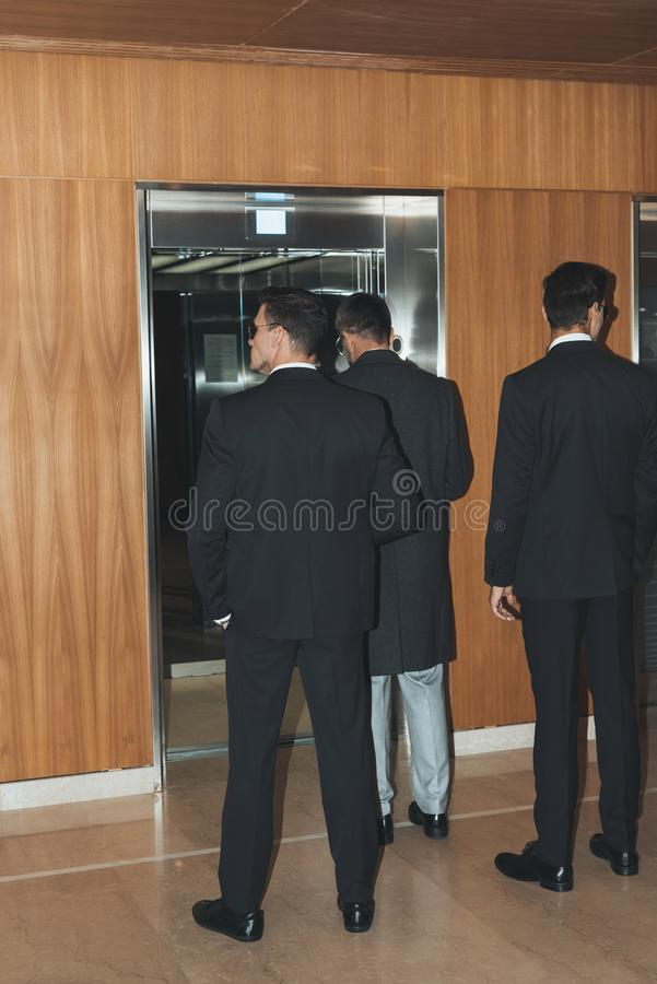Rear view of bodyguards and politician standing at elevator stock images