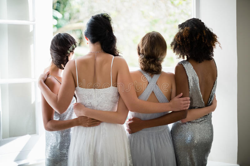 Rear view of bride and bridesmaids standing together near window royalty free stock photos