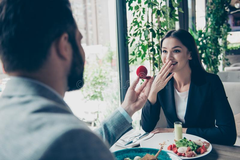 Rear view of a brunet bearded man proposing to his cute shocked. Rear view of a brunet bearded men proposing to his cute shocked brunette lady in a nice royalty free stock image