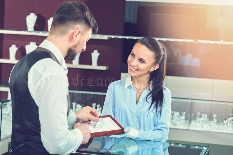 Rear view of brunet man buying jewelry for girlfriend. stock photo