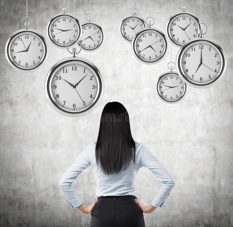 A rear view of a brunette business lady who is looking at the hovering pocket watches in the air. A concept of a value of time in. Business. Concrete background stock photos