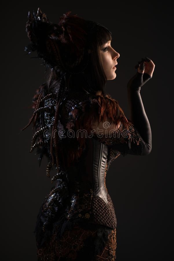 Rear view of brunette gothic woman. In studio on the dark background stock image