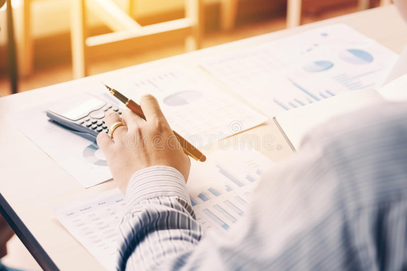 Rear view of business asian man calculate with analyze result summary report on desk in company office room. royalty free stock images