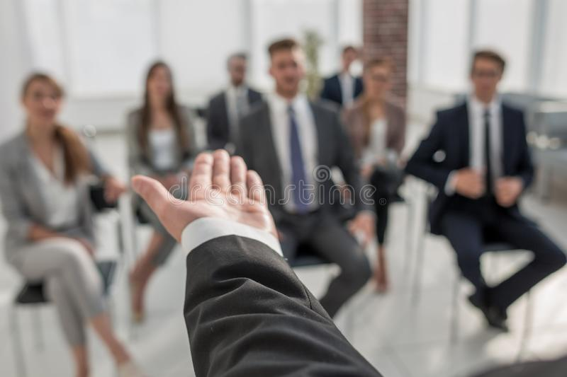 Rear view.Business coach gesturing his hand in front of a group of people. royalty free stock image